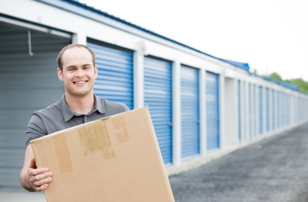 a man carrying a cardboard box in front of a storage facility