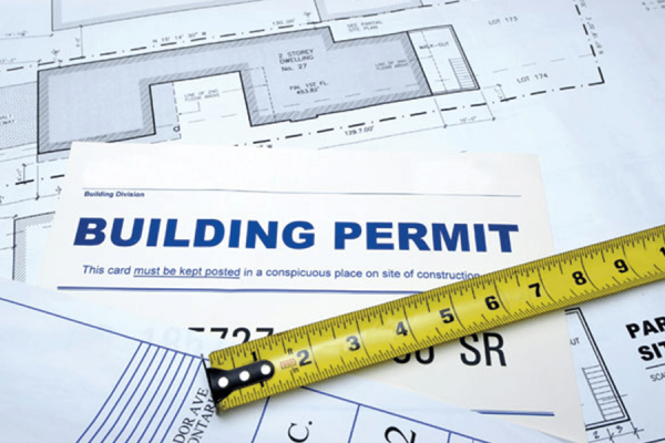 a measuring tape over a business permit