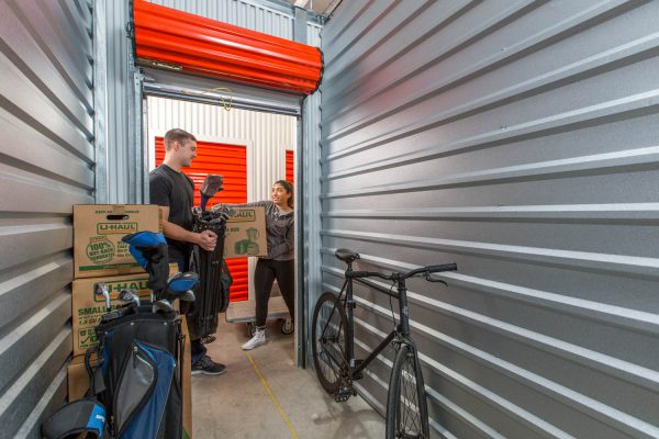 Two siblings putting their things in a self storage unit