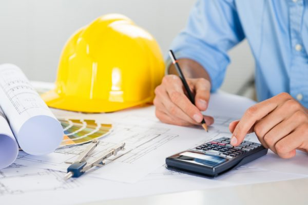 An architect using a calculator to compute construction costs