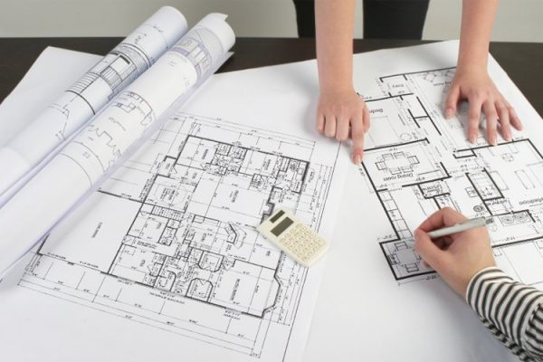 Two draftsmen making a floorplan on the table